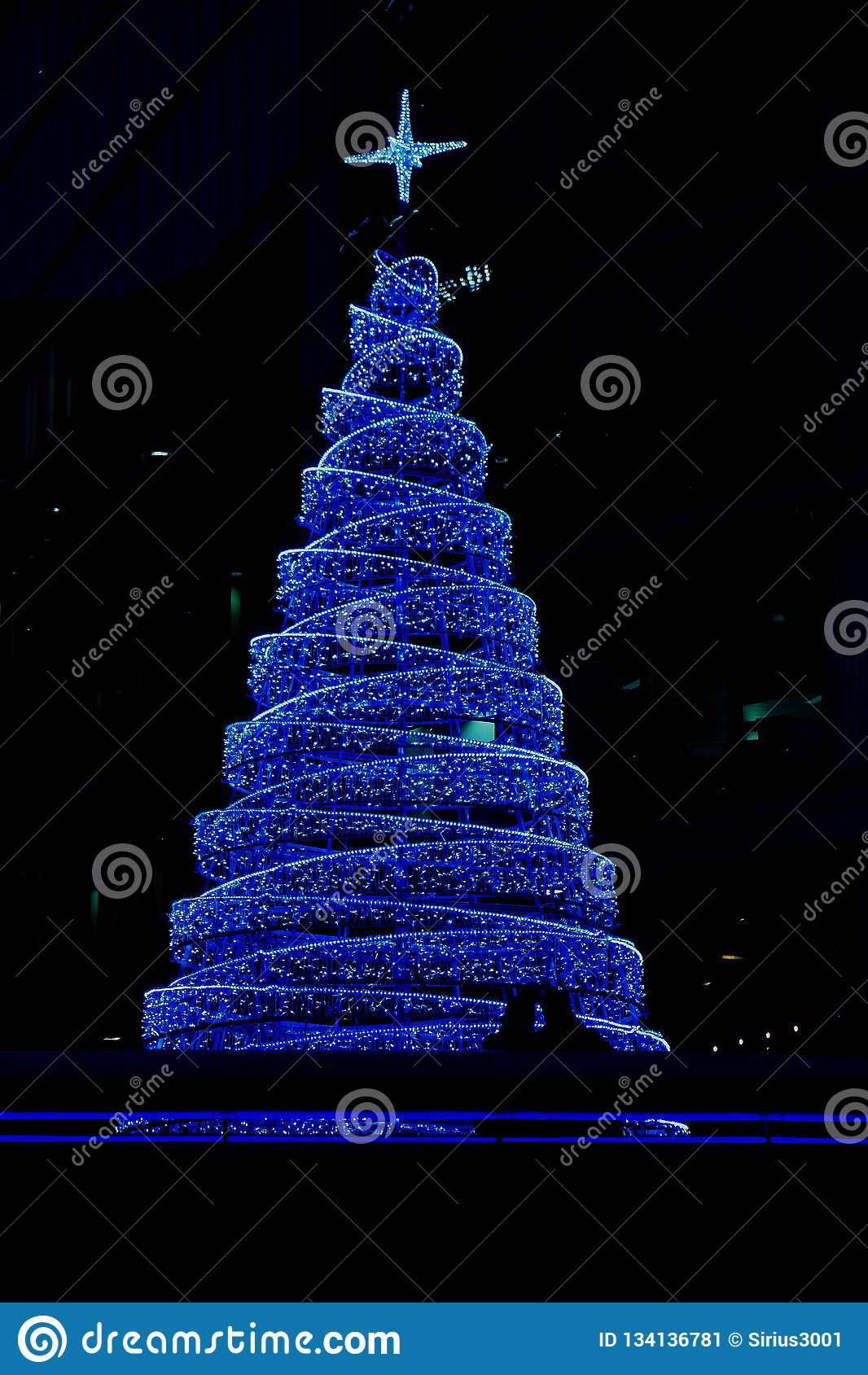 Photo of large blue Christmas tree at mall in London near the tower bridge at christmastime