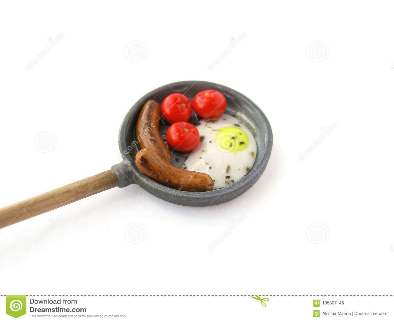 Photo Miniature fake Frying pan with fried egg, tomatoes and sausages on white background. Dollhouse miniature, polymer clay toy,