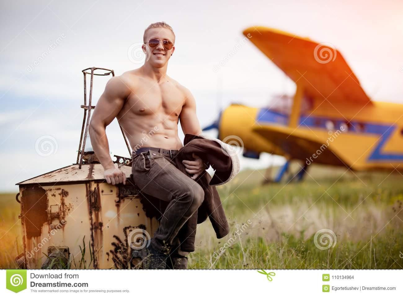 Photo of naked model which is sitting and smile in front of airplane .