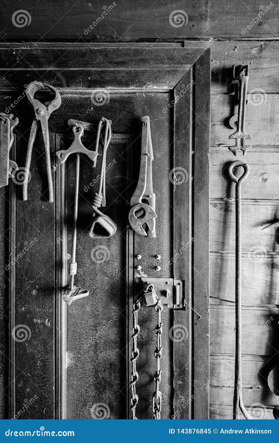 Photo noire et blanche de vieux outils accrochés sur une porte