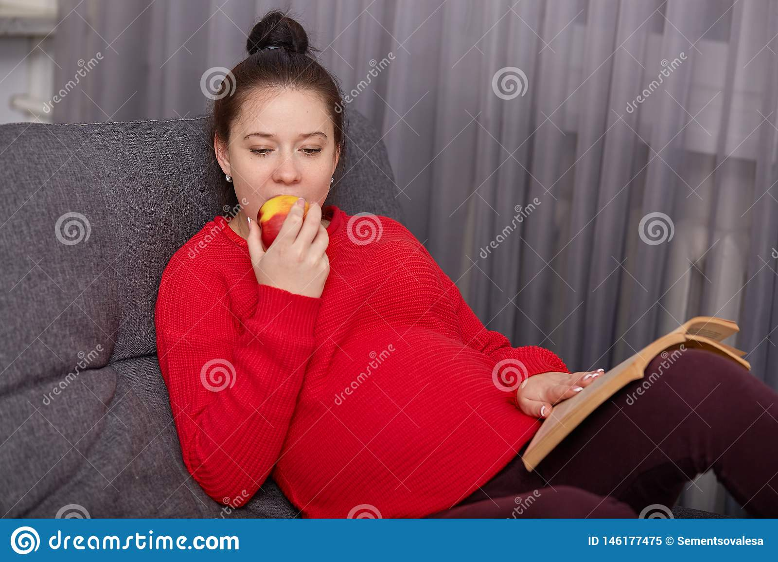 Photo of pregnant woman wears red sweater and maroon leggins, lies on comfortable grey sofa, eating apple, reading book about