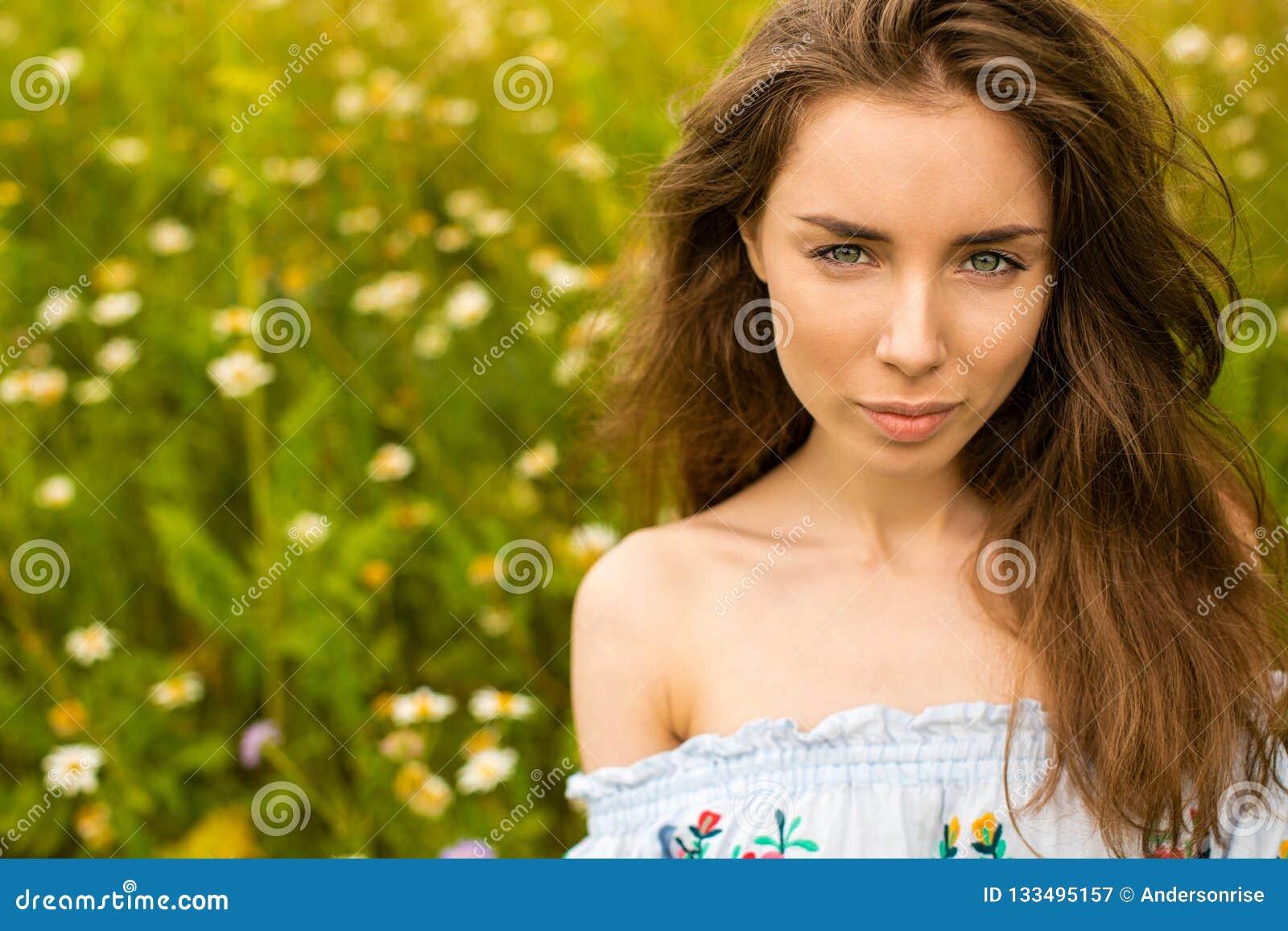 Photo of pretty brunette woman in chamomile field