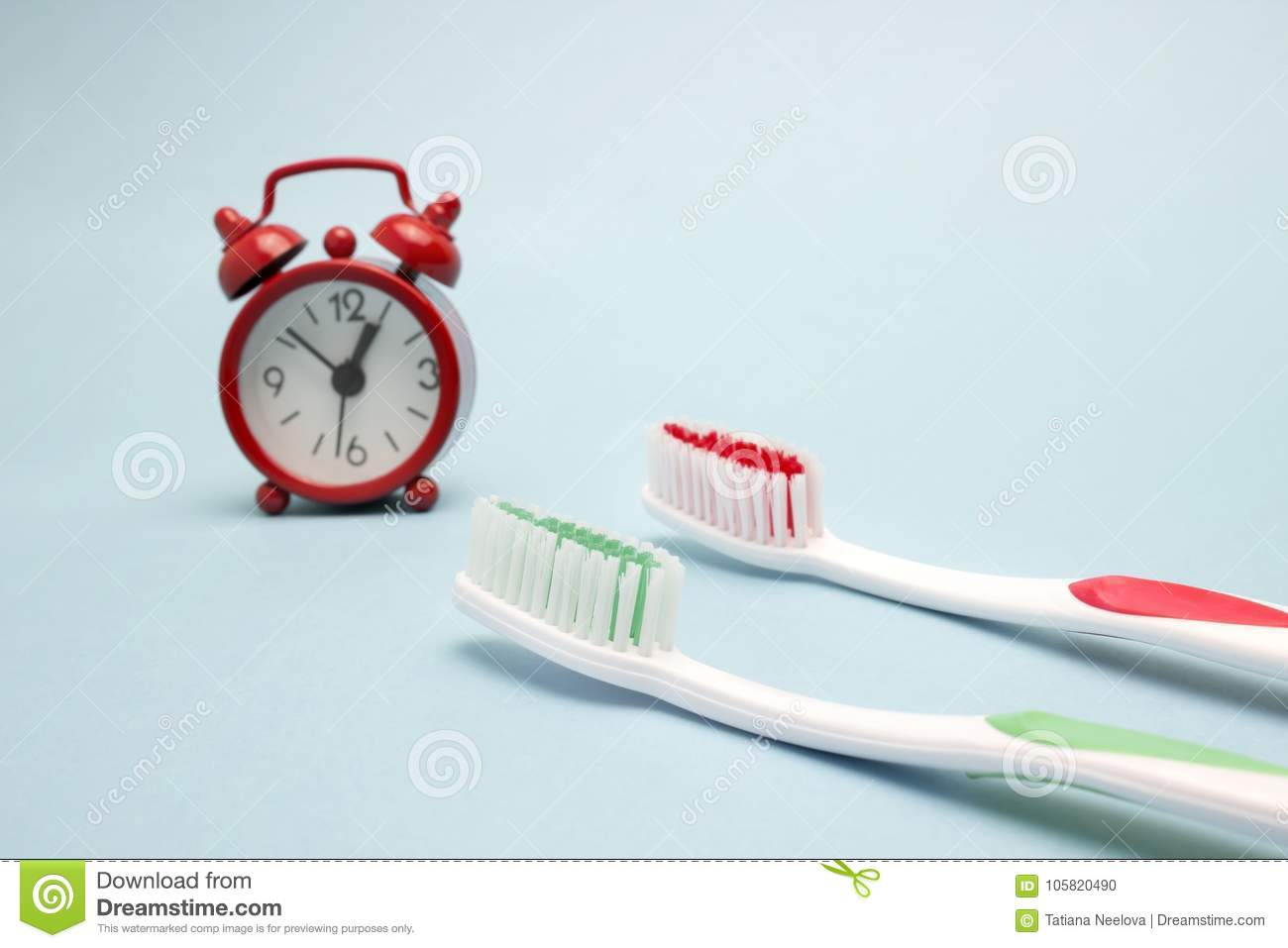 A photo of the red alarm clock and two toothbrushes. Time to clean the teeth. Dental care, personal hygiene concept photo. An impo