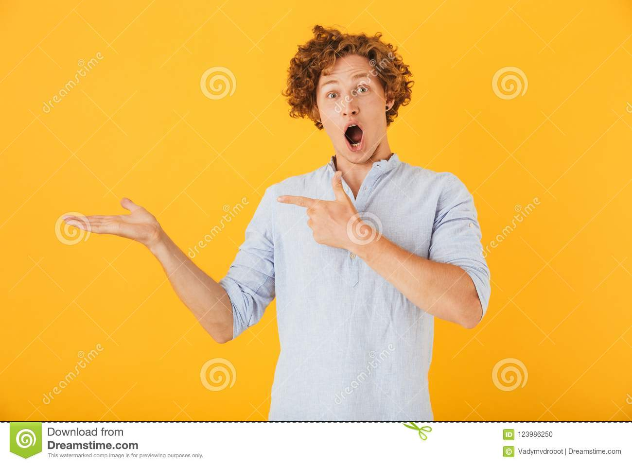 Photo of shocked european man 20s shouting and holding copyspace at palm, isolated over yellow background