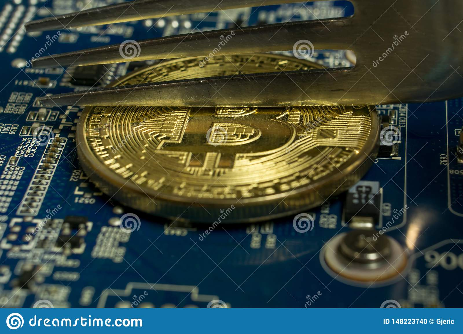 A single Bitcoin coin on the blue computer motherboard and fork trying to half it