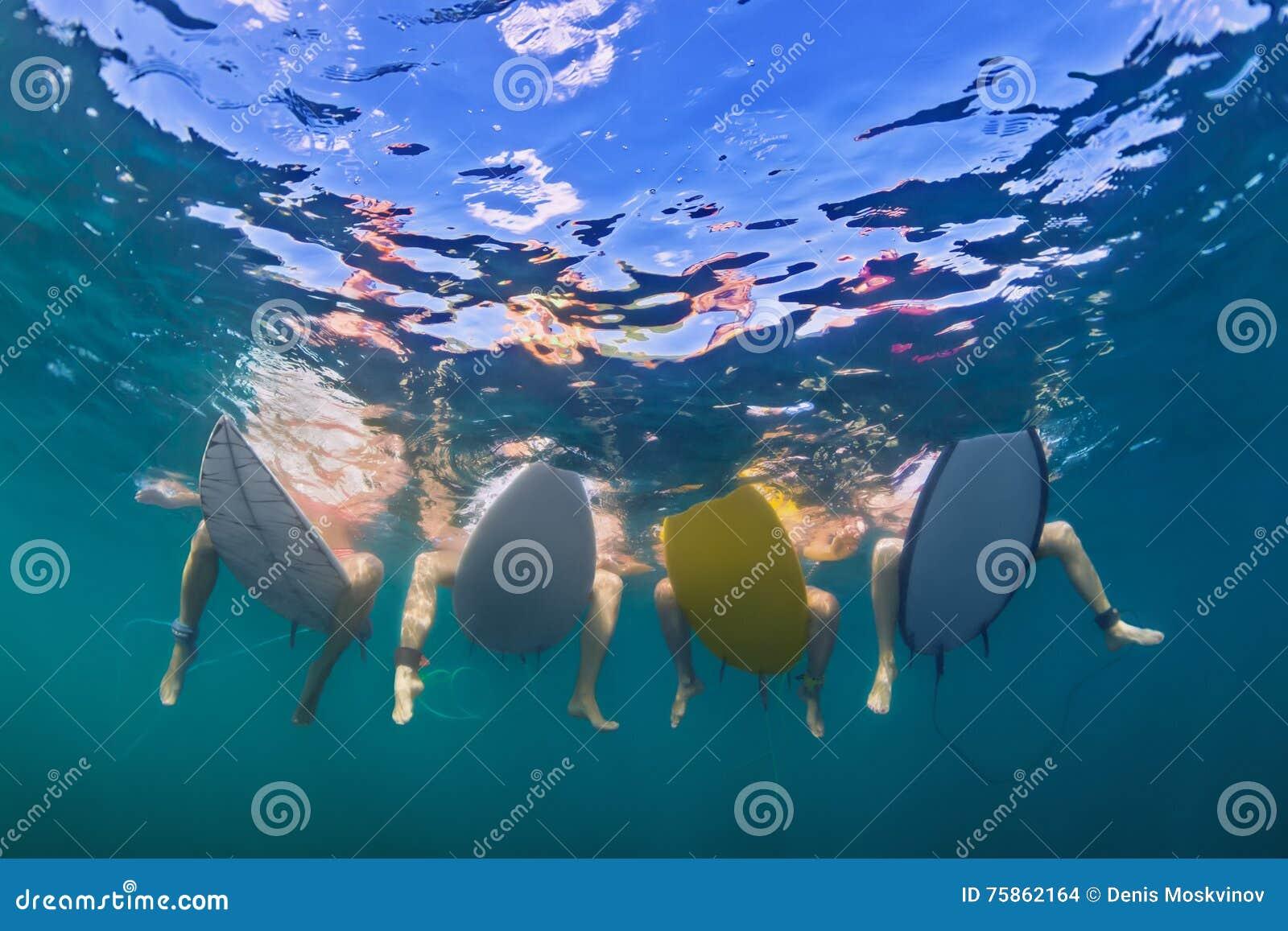 Photo sous-marine des surfers s asseyant sur des panneaux de ressac