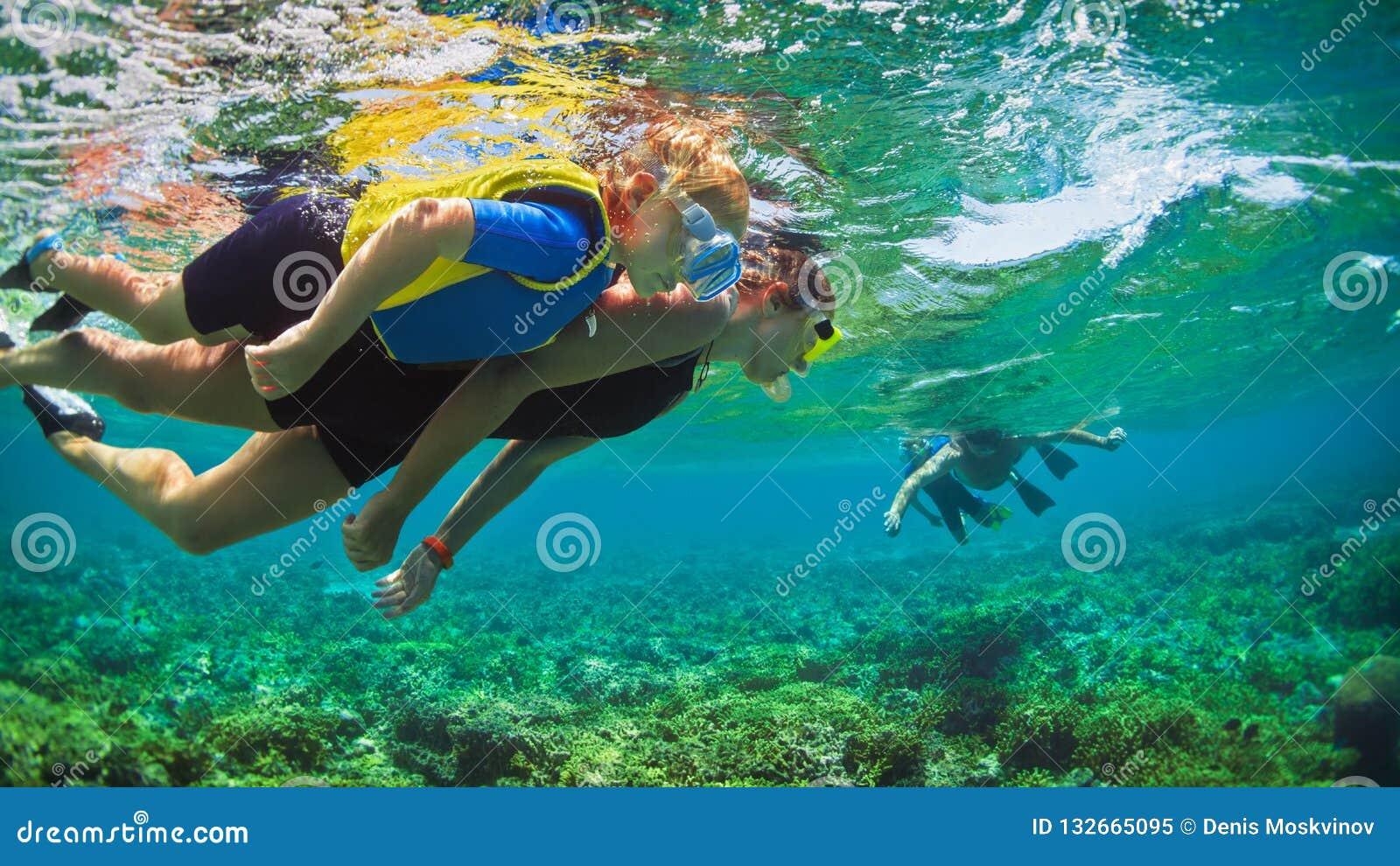 Photo sous-marine Famille heureuse naviguant au schnorchel en mer tropicale