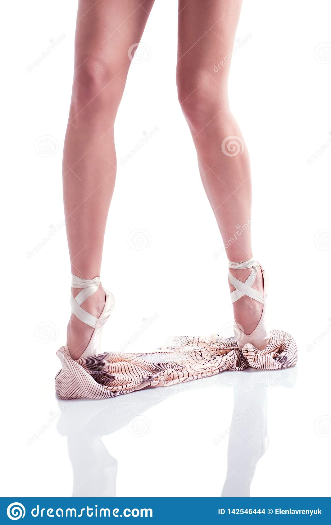 Ballerina`s feet in pointe and with silk scarf on white background