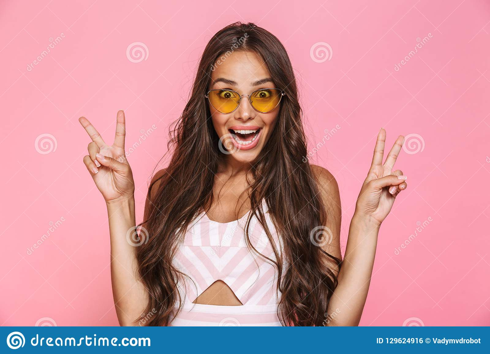Photo of stylish woman 20s wearing sunglasses rejoicing with surprise, isolated over pink background