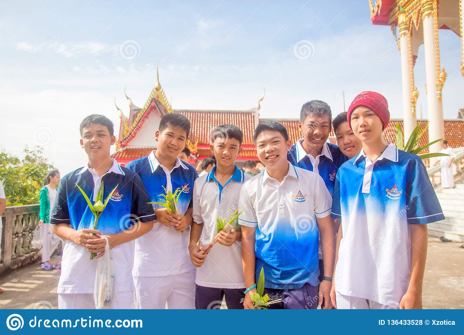 Thai students wear white clothes making a merit at the temple in Pranburi, Thailand July 21,2017