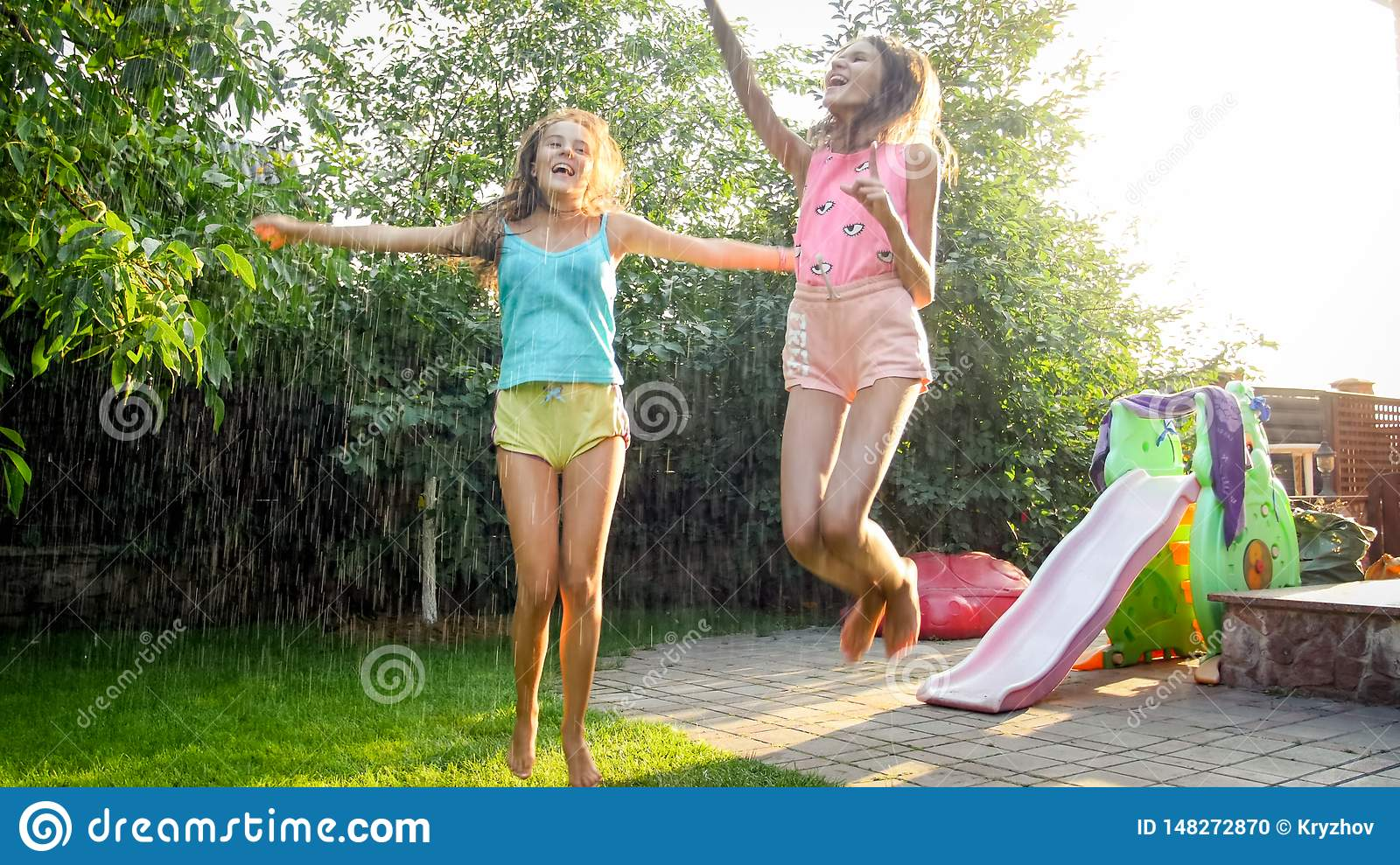 Photo of two happy laughing sisters in wet clothes dancing under water droplets from garden hose at garden. Family