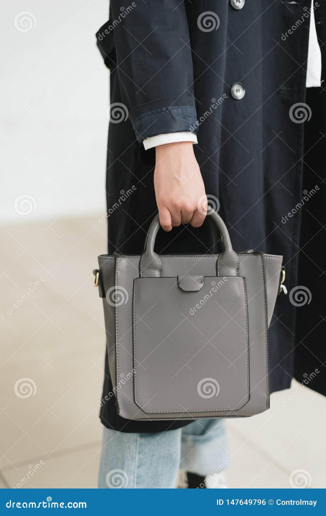 Photo verticale d une fille dans un sac bleu-gris dans les mains