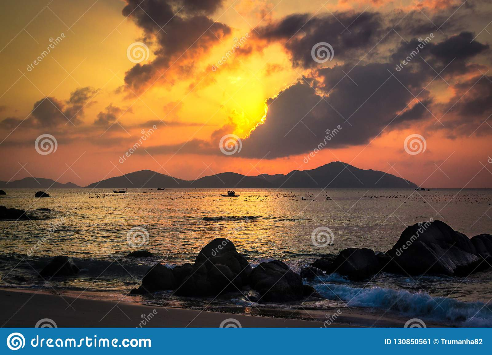 Nature Seascape with Tranquil Beach, Boulders, Islands, Dark Clouds and Hidden Sun at Sunrise