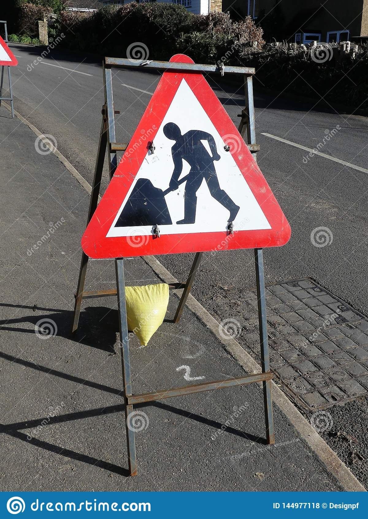 Triangular road works sign on metal frame by roadside