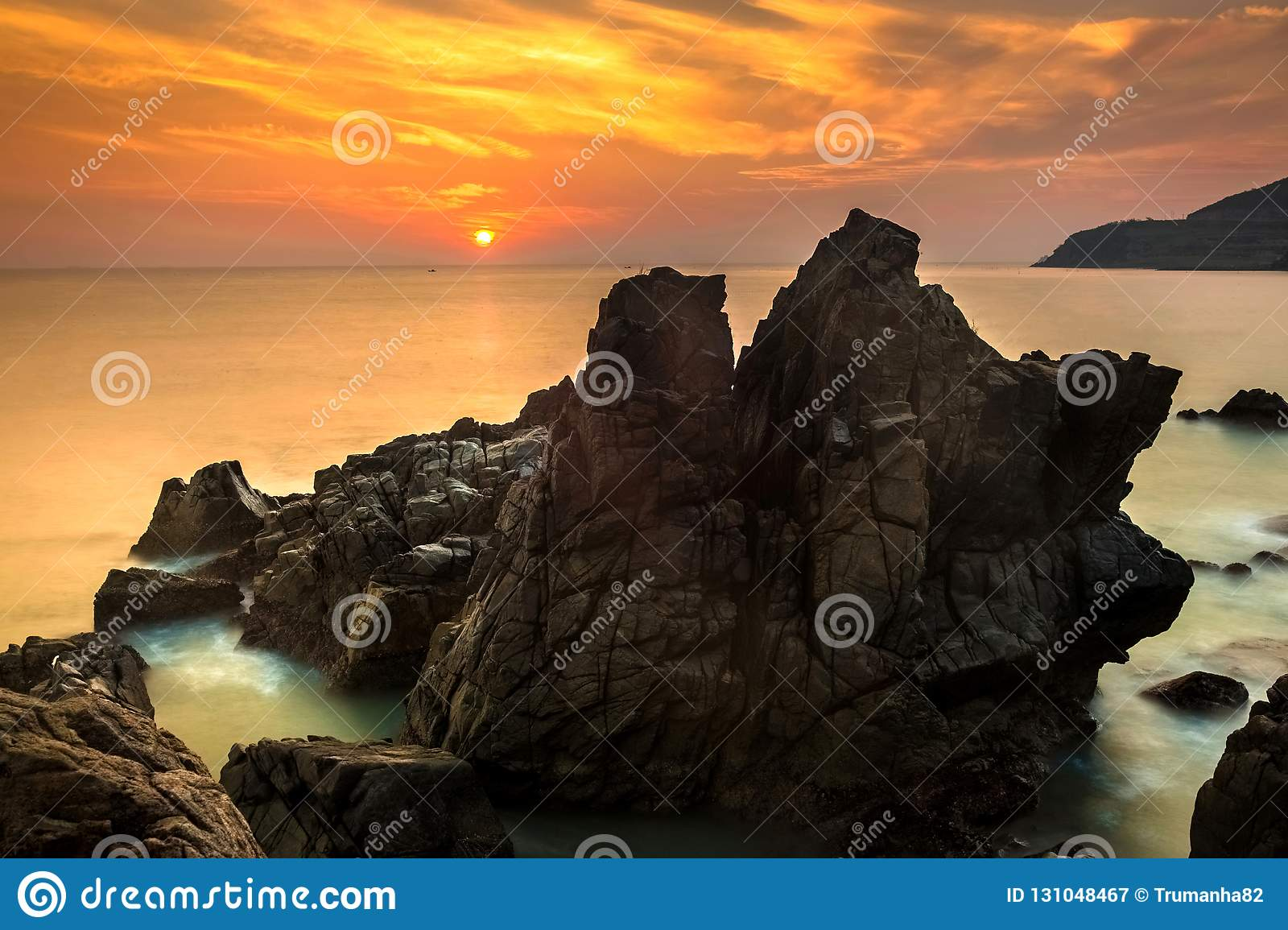 Nature Seascape with Exotic Boulders, Silky Water at Gorgeous Orange Sunrise