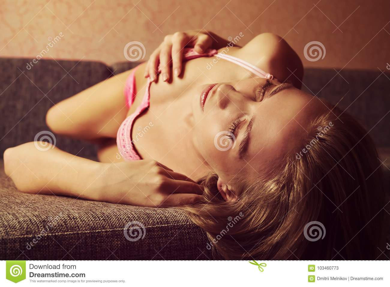 d79d66567c Photo of woman lying in bed and touching breast in bra. Cute Blonde lies on  the couch and touching her Boobs in pink bra.