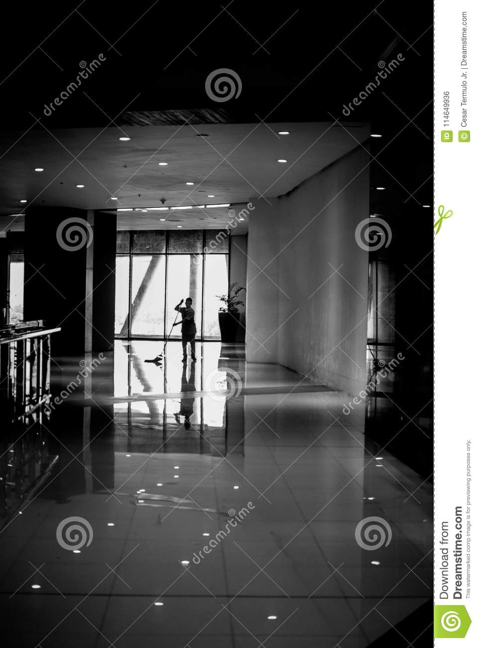 Photo of a working person cleaning the floor of a mall in black and white for commercial purposes
