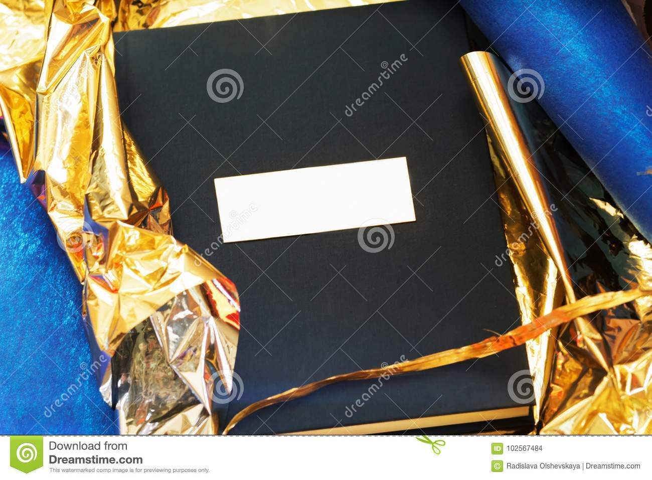 A photobook with a cover of a blue takani in a gift gold wrapper.