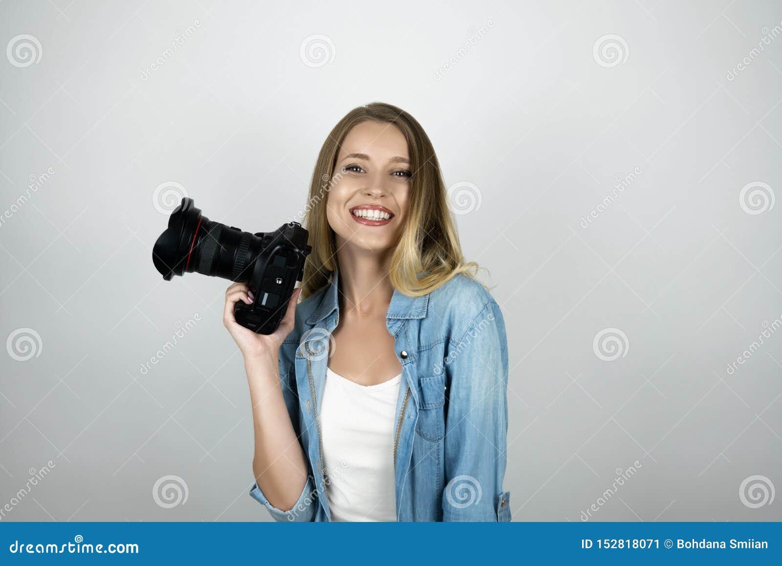 Photocamera rubio feliz de la tenencia de la mujer joven en su fondo blanco aislado sonriente de la mano