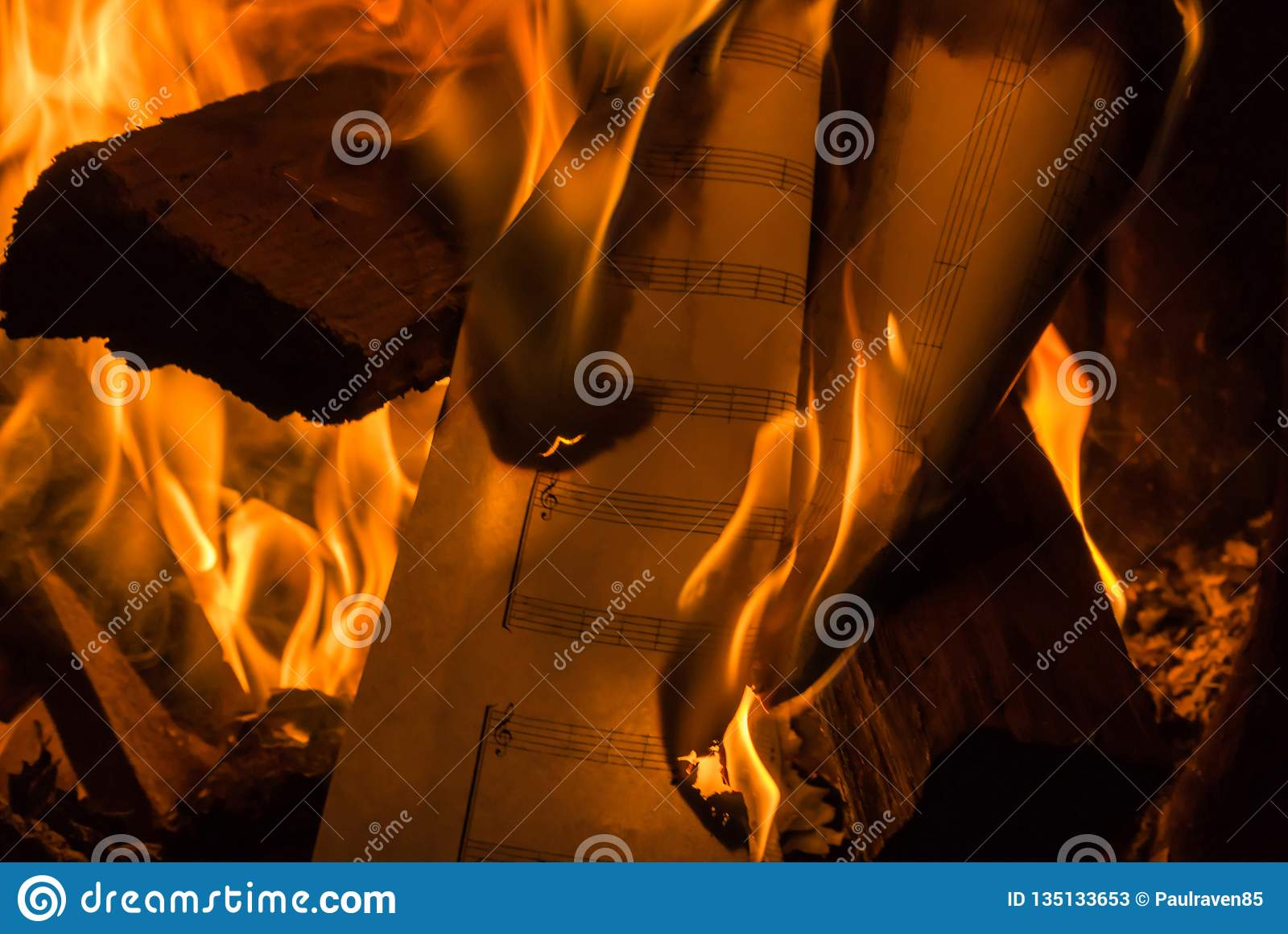 Photograph Of A Burning Blank Sheet Of Music Among Logs In