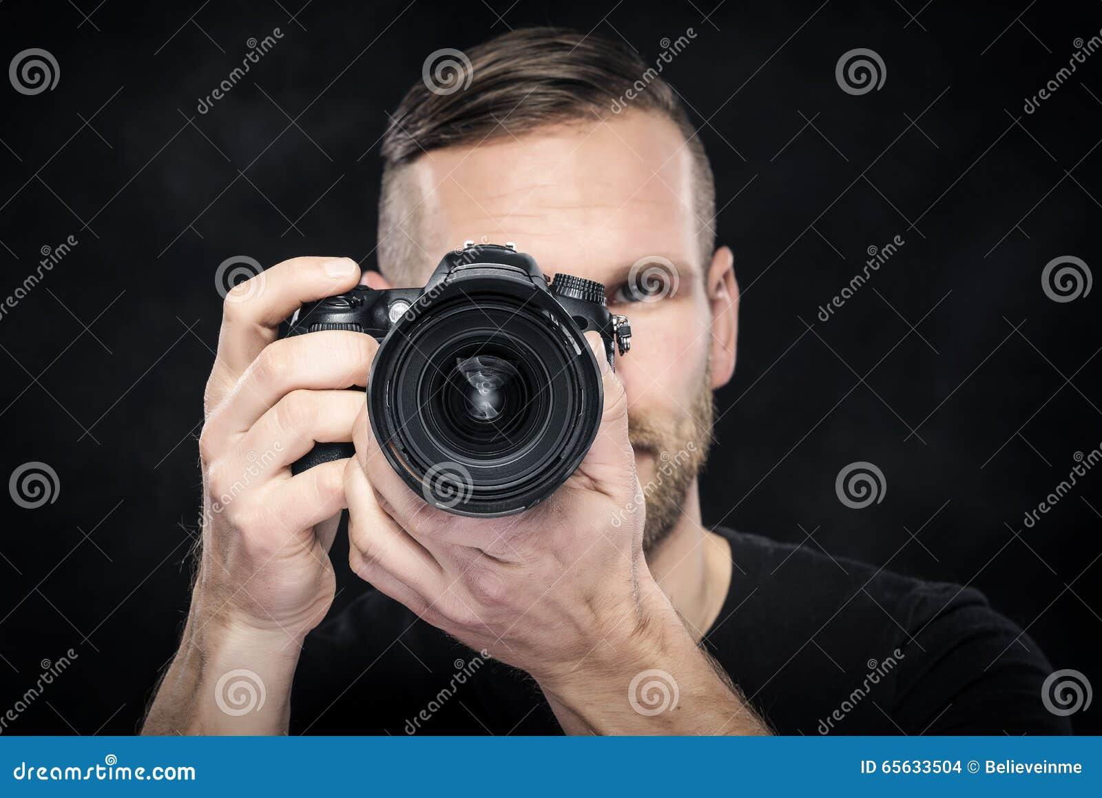 Photographe avec l appareil-photo sur le noir