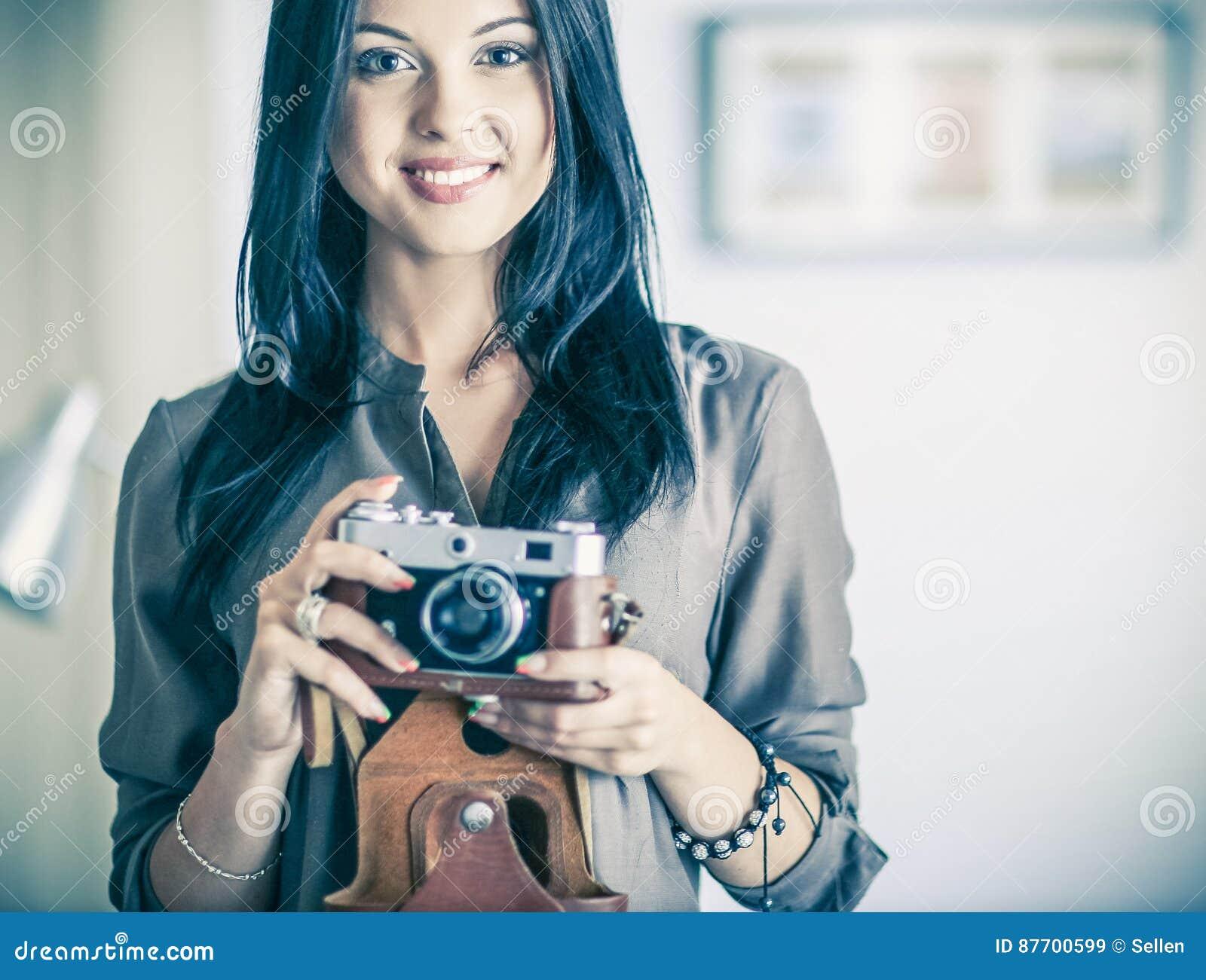 Photographe féminin s asseyant sur le bureau avec l ordinateur portable