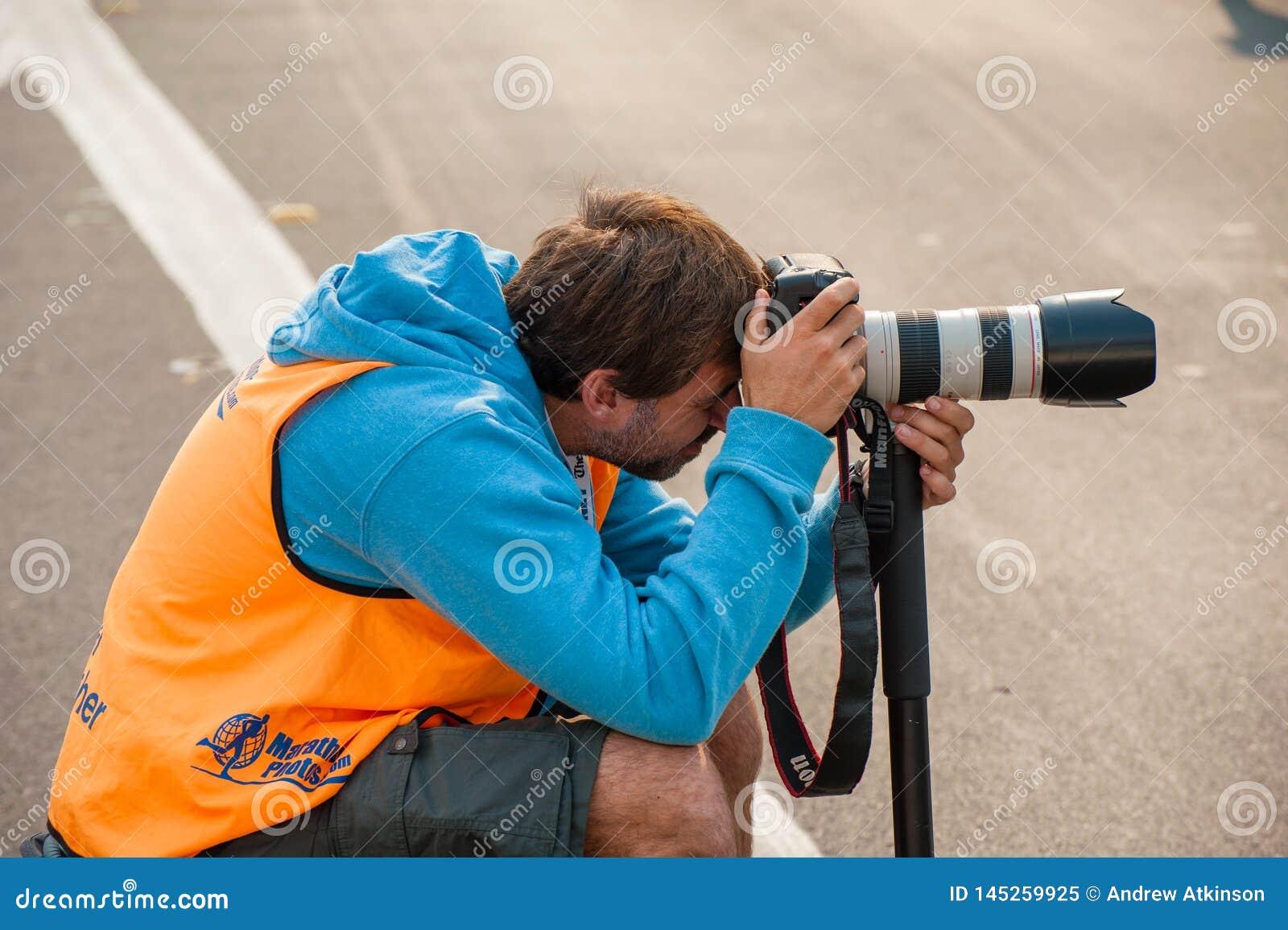 Photographe officiel se tapissant prenant des photos avec un DSLR et un zoom