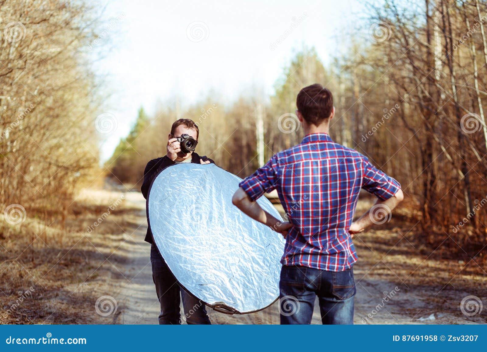 Photographe Photographing Male Model en Forest Backstage de mode Photoshoot par le photographe professionnel avec DSLR