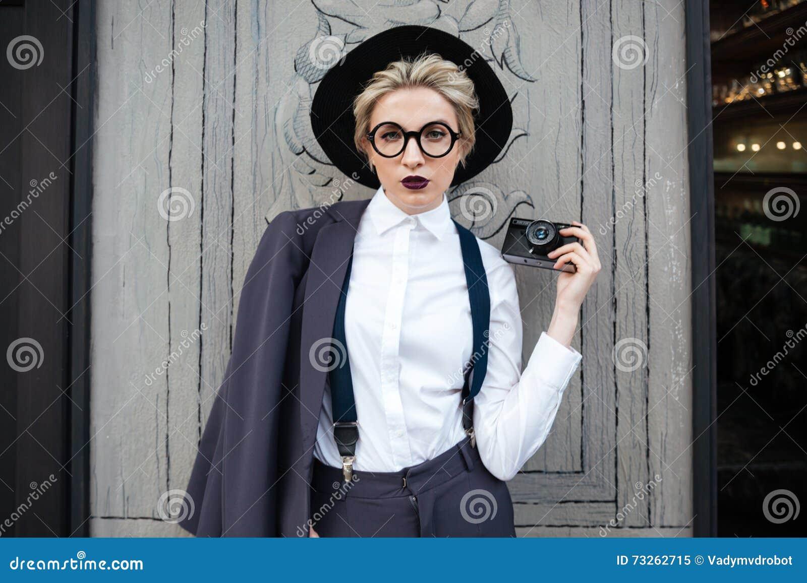 Photographe sérieuse de jeune femme avec l appareil-photo de photo