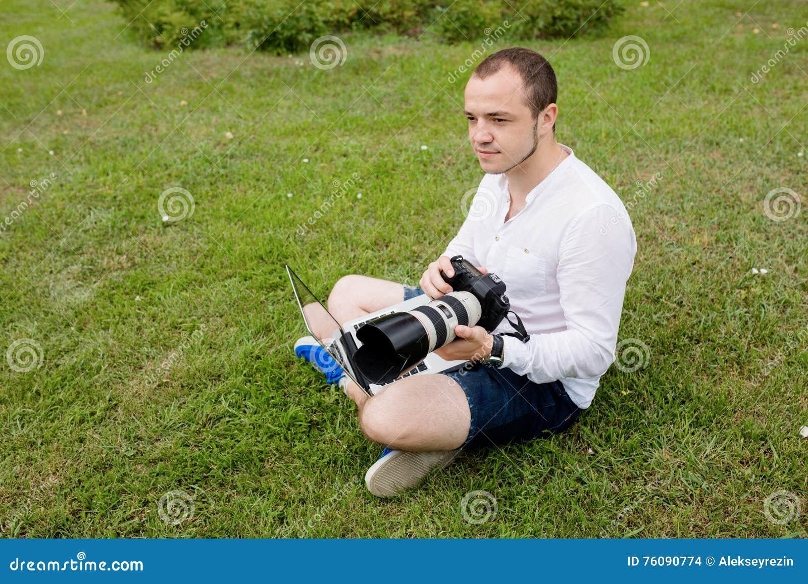 Photographe travaillant sur un ordinateur portable dehors