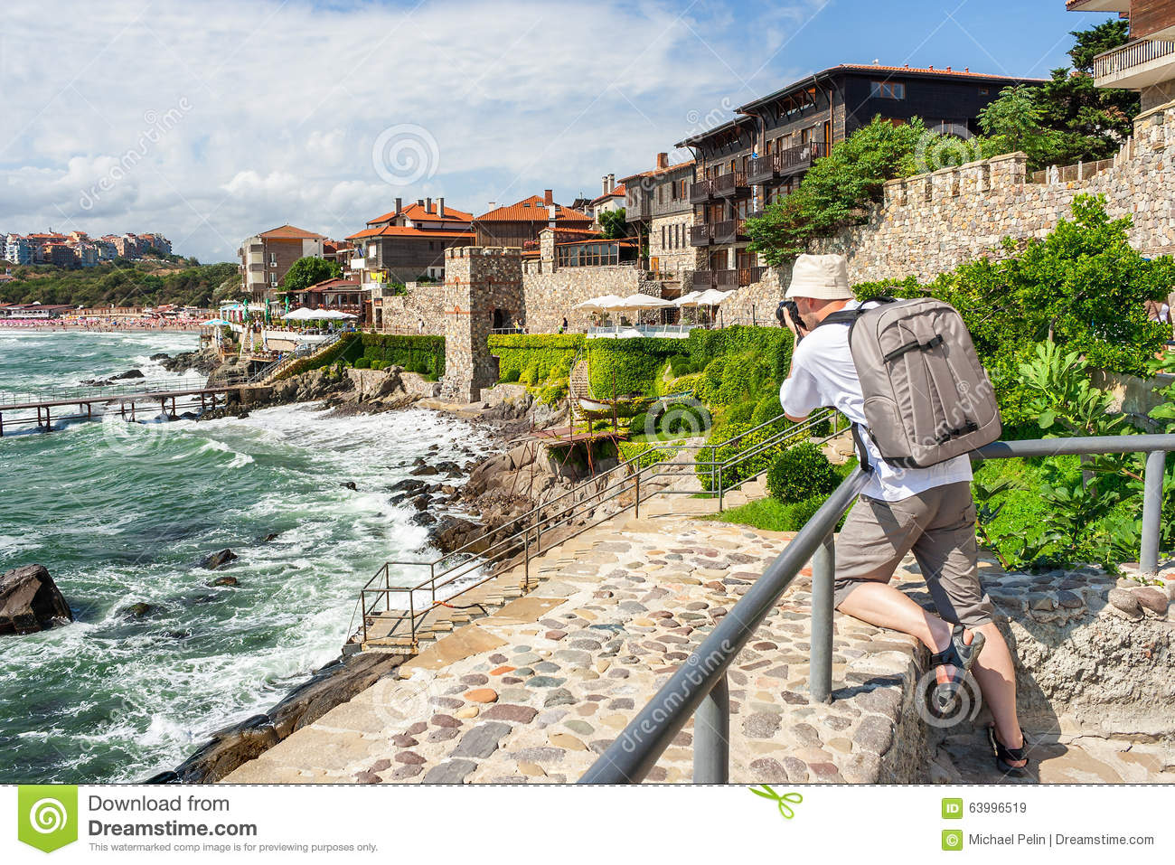 Photographer with backpack shooting in old town Sozopol near sea