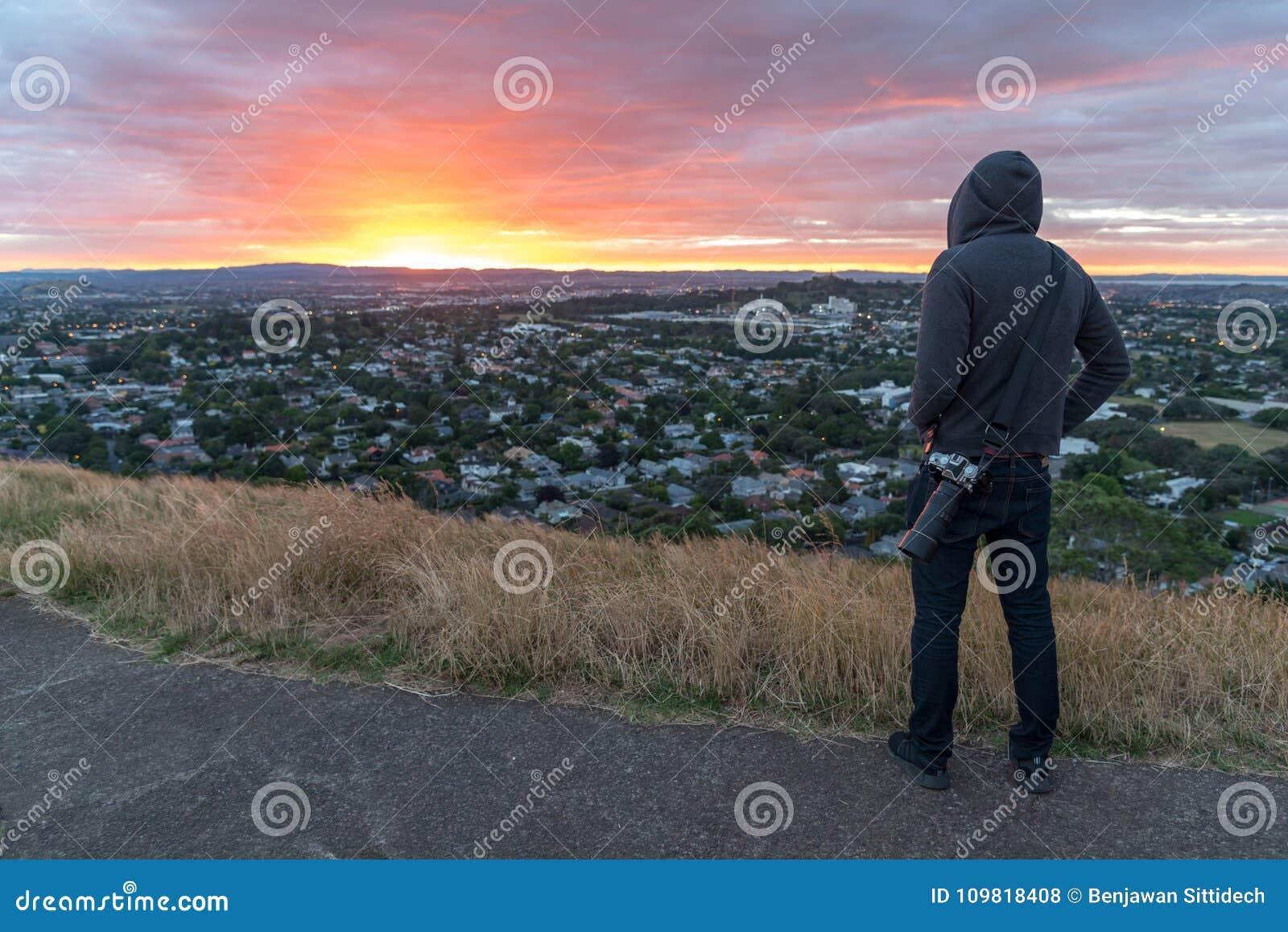 Photographer man wearing hoody watching sunrise over Auckland ci