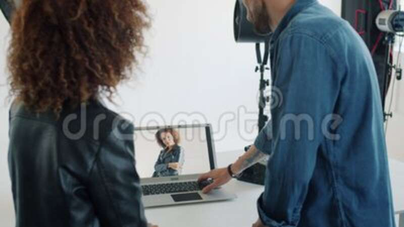 Photographer showing photos to mixed race model using laptop computer in studio