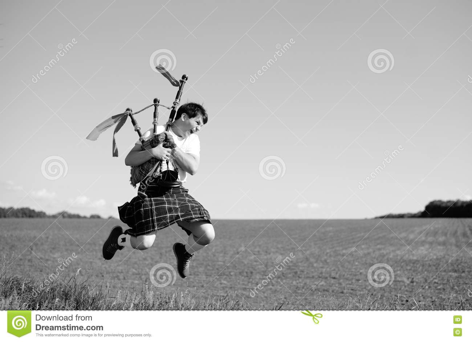Photographie blanche noire de l homme sautant haut avec des tuyaux dans le kilt traditionnel écossais sur le champ d été dehors