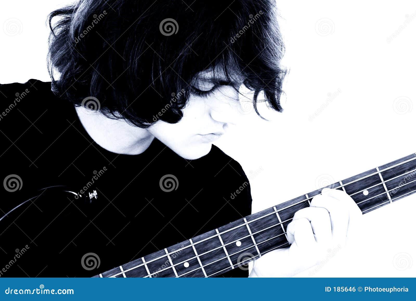 Photographie courante : Jeune garçon de l adolescence jouant la guitare basse