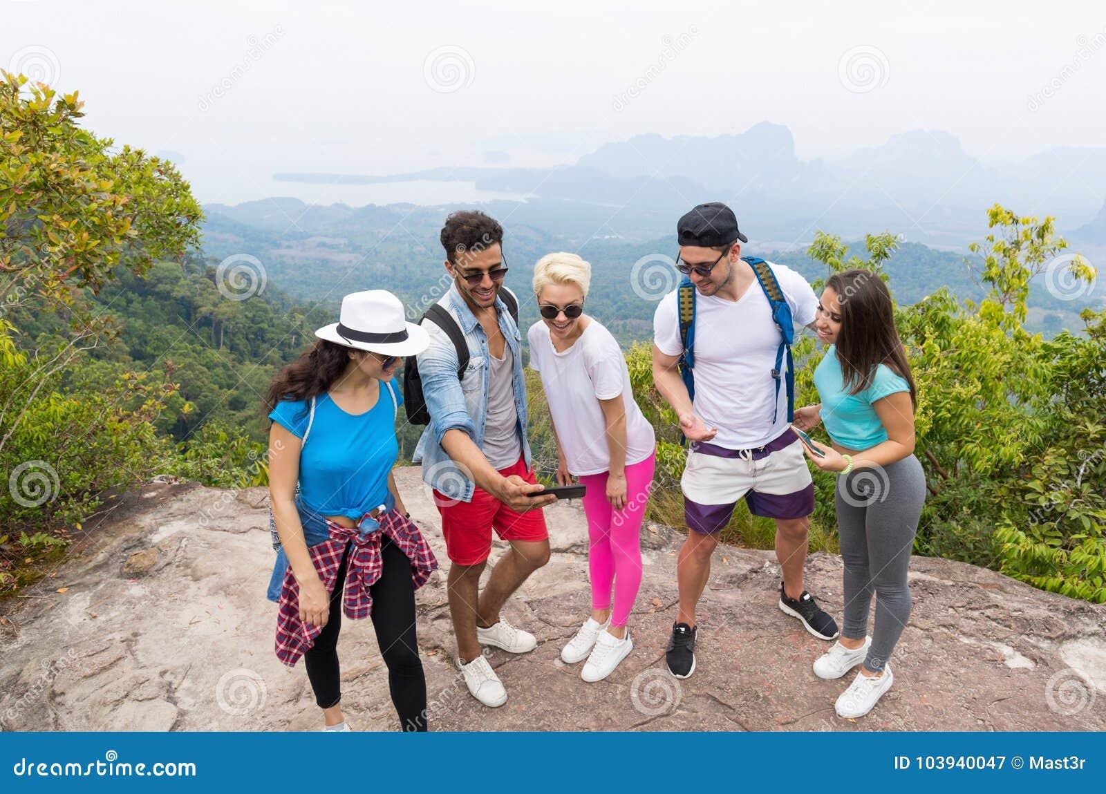 Photos de touristes de montre de groupe aux téléphones intelligents de cellules, les gens avec le sac à dos au-dessus du paysage