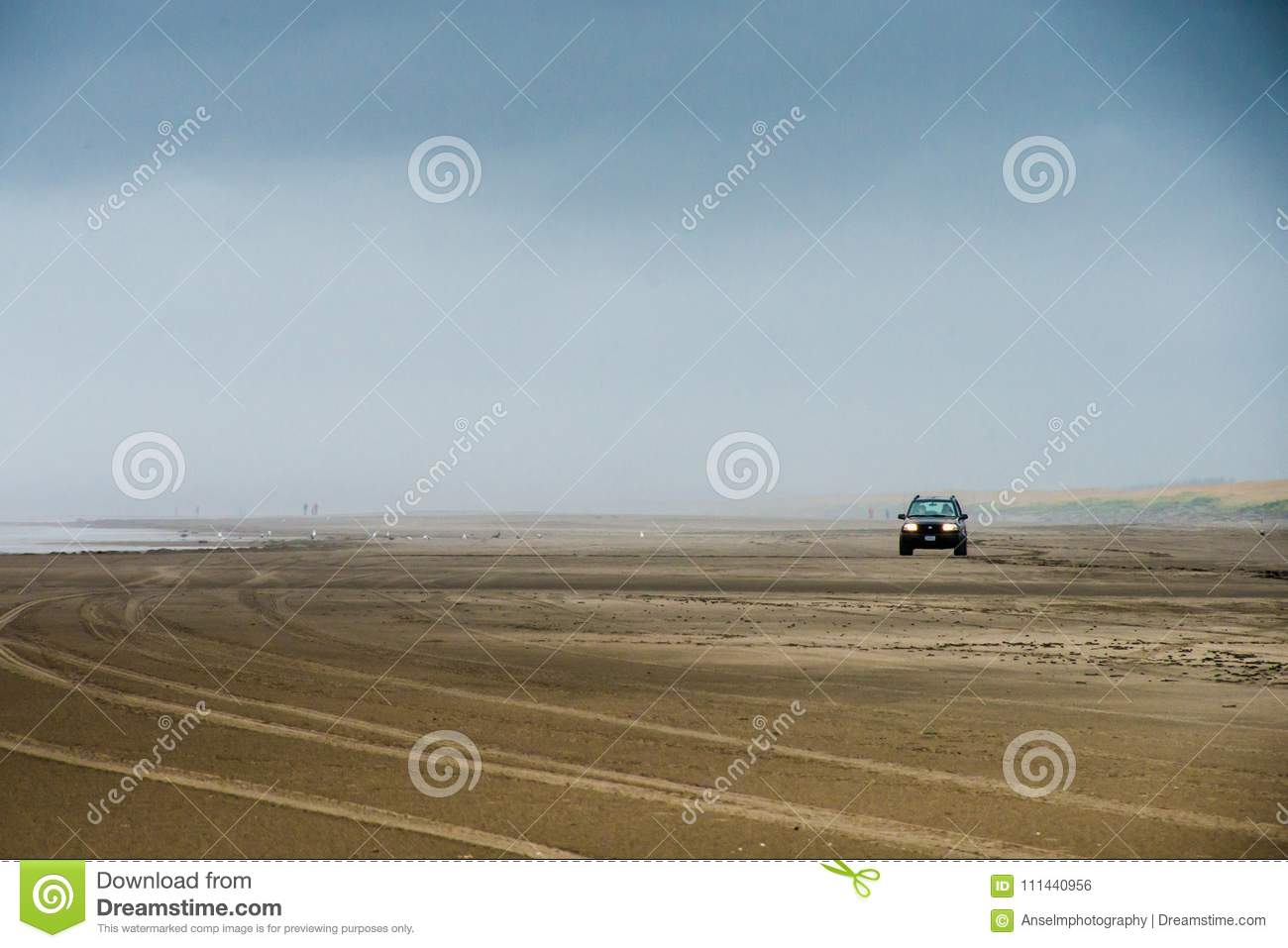A Lone Car Driving On A Large Field Of Sand Beach In Foggy