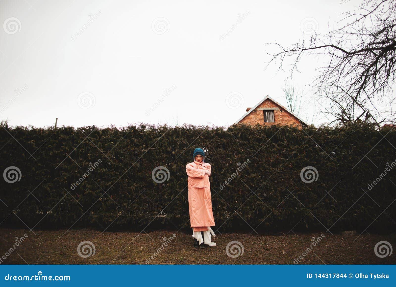 Photosession av en härlig flicka i en vit klänning på bakgrunden av gran-träd fäktar