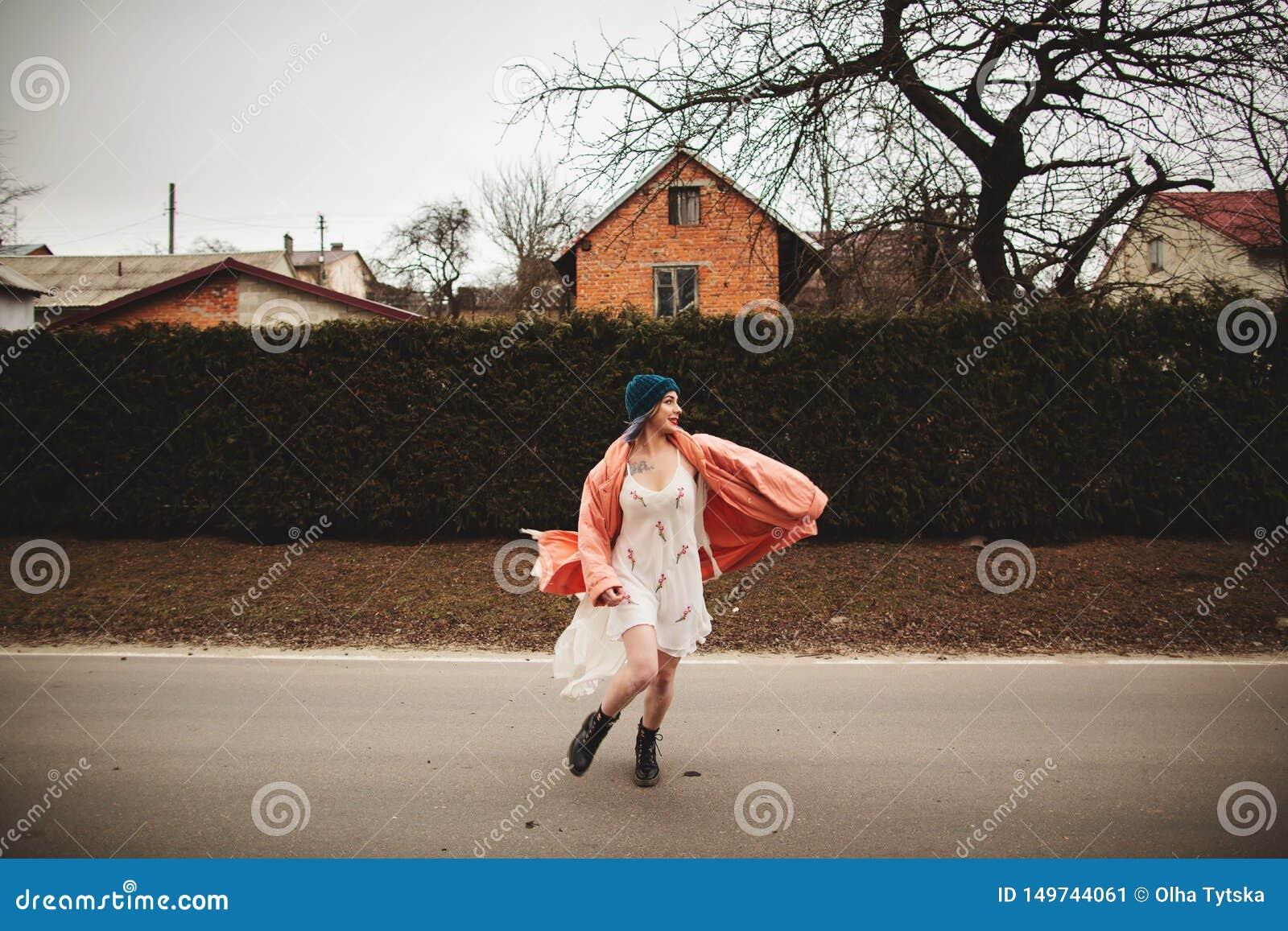 Photosession d une belle fille dans une robe blanche sur le fond de la barri?re de sapins