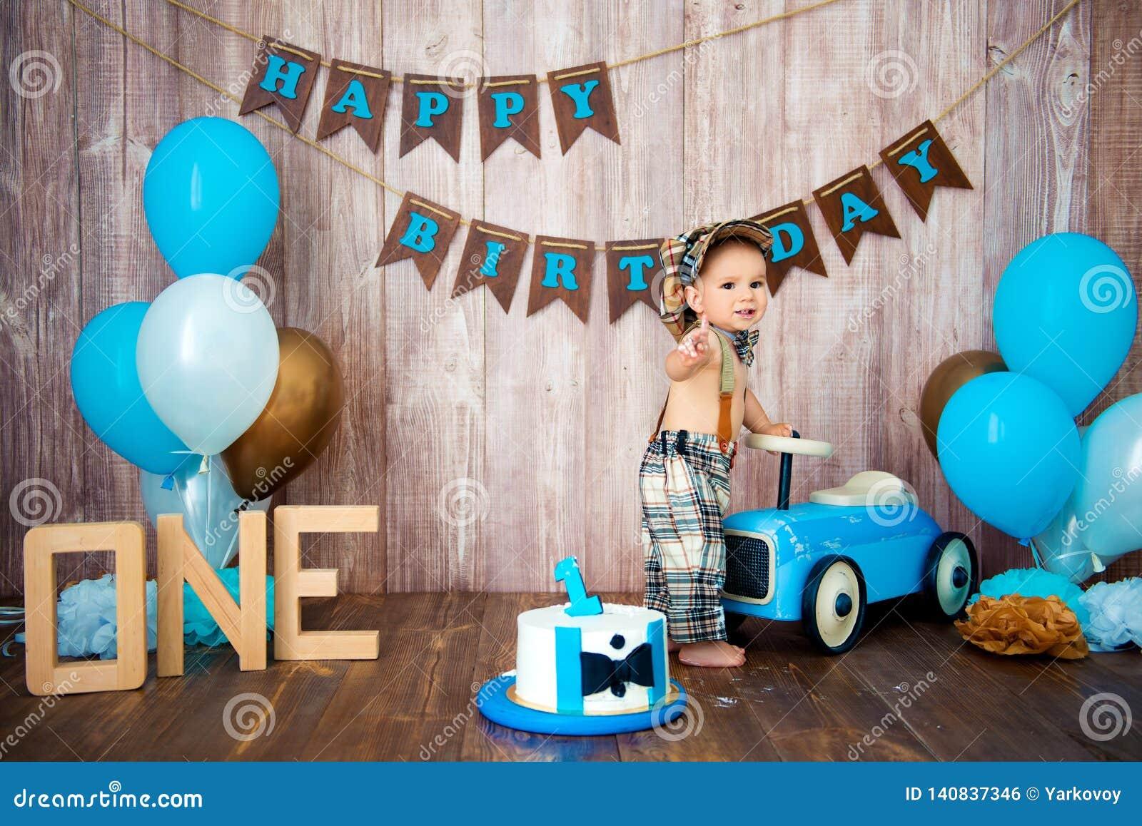 Photoshoot一个小男孩绅士的易碎smashcake 与一辆木减速火箭的汽车和氦气气球的装饰的photozone 愉快