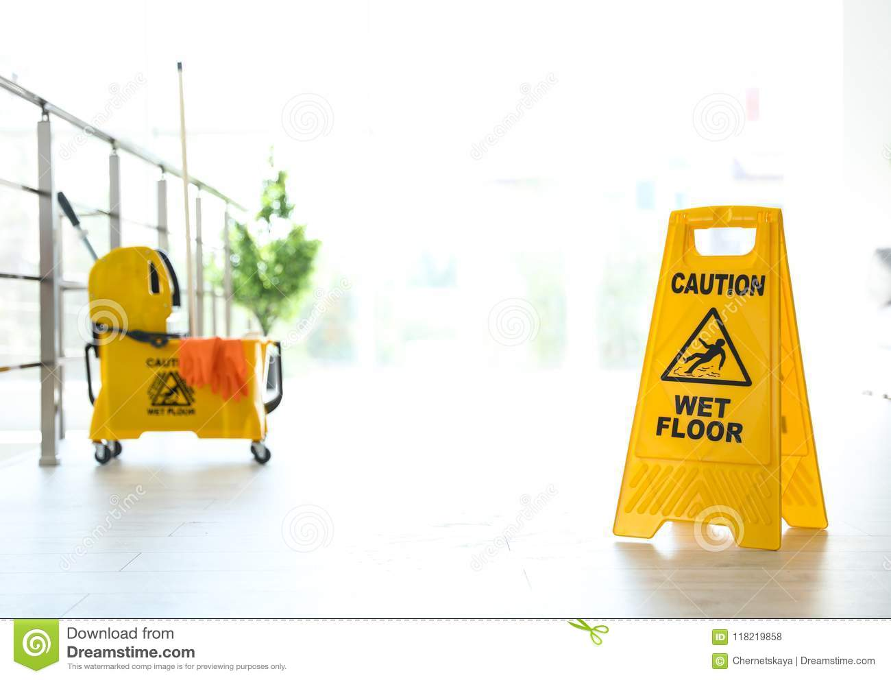 Phrase CAUTION WET FLOOR on safety sign and yellow mop bucket with cleaning supplies, indoors