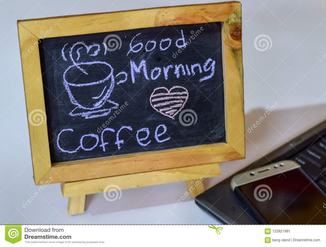 Phrase Good Morning coffee written on a chalkboard on it and smartphone, laptop