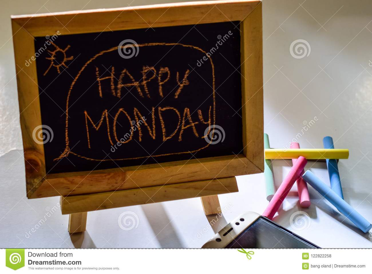 Phrase happy monday written on a chalkboard on it and smartphone, colorful chalk