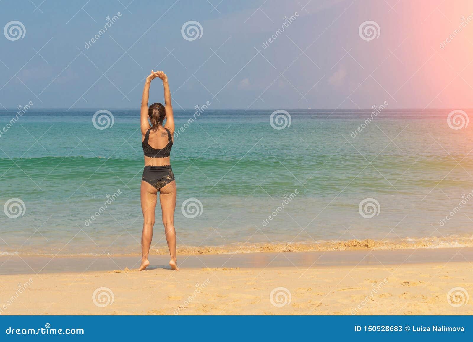 Phuket, Tailandia - 30 de marzo de 2019: Muchacha delgada en un bañador negro con un tatuaje en su hombro que hace la yoga Pilate