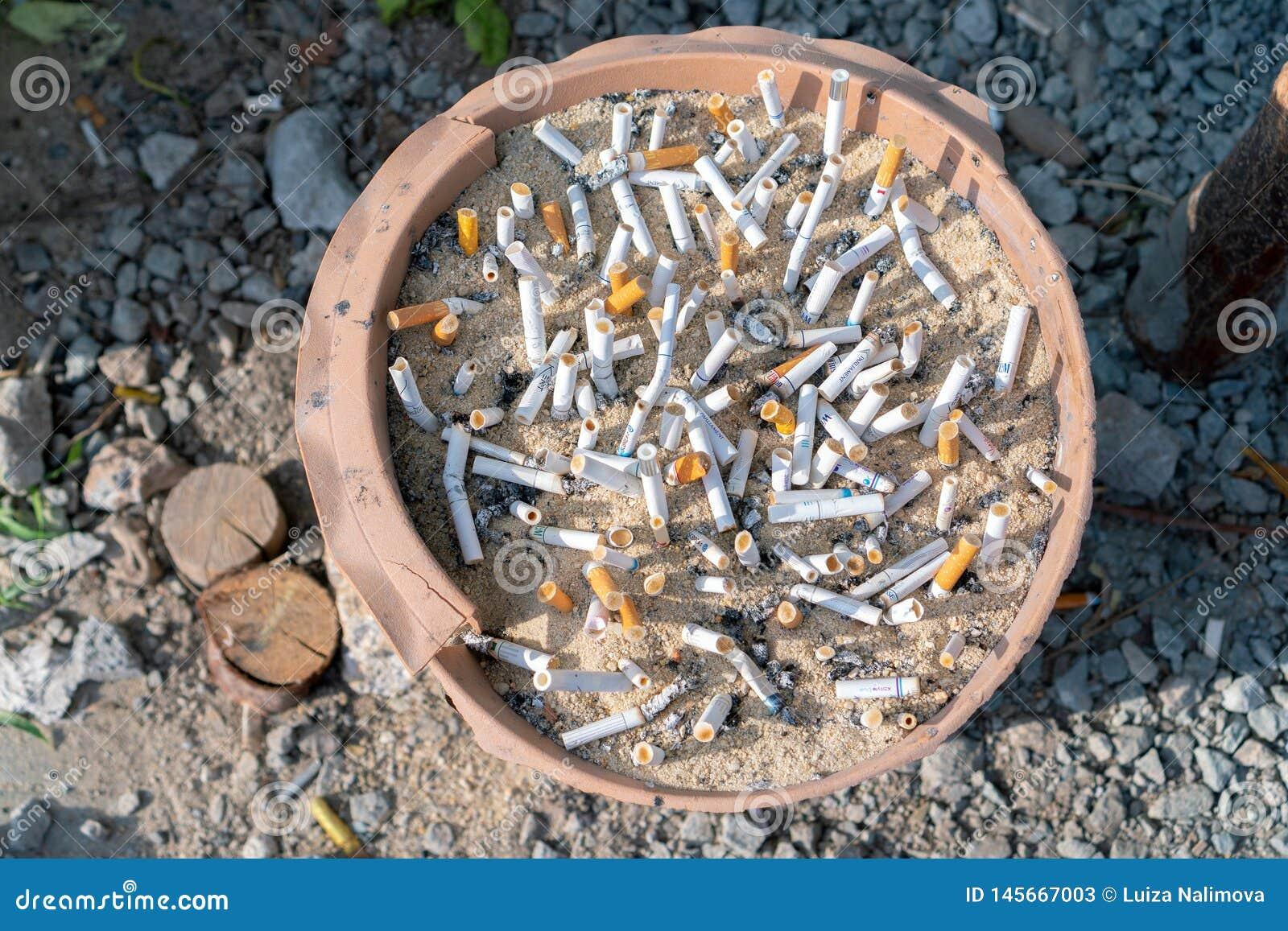 Phuket Tajlandia, Marzec, - 27, 2019: Papierosowi krupony w ashtray z piaskiem przy dymienie punktem