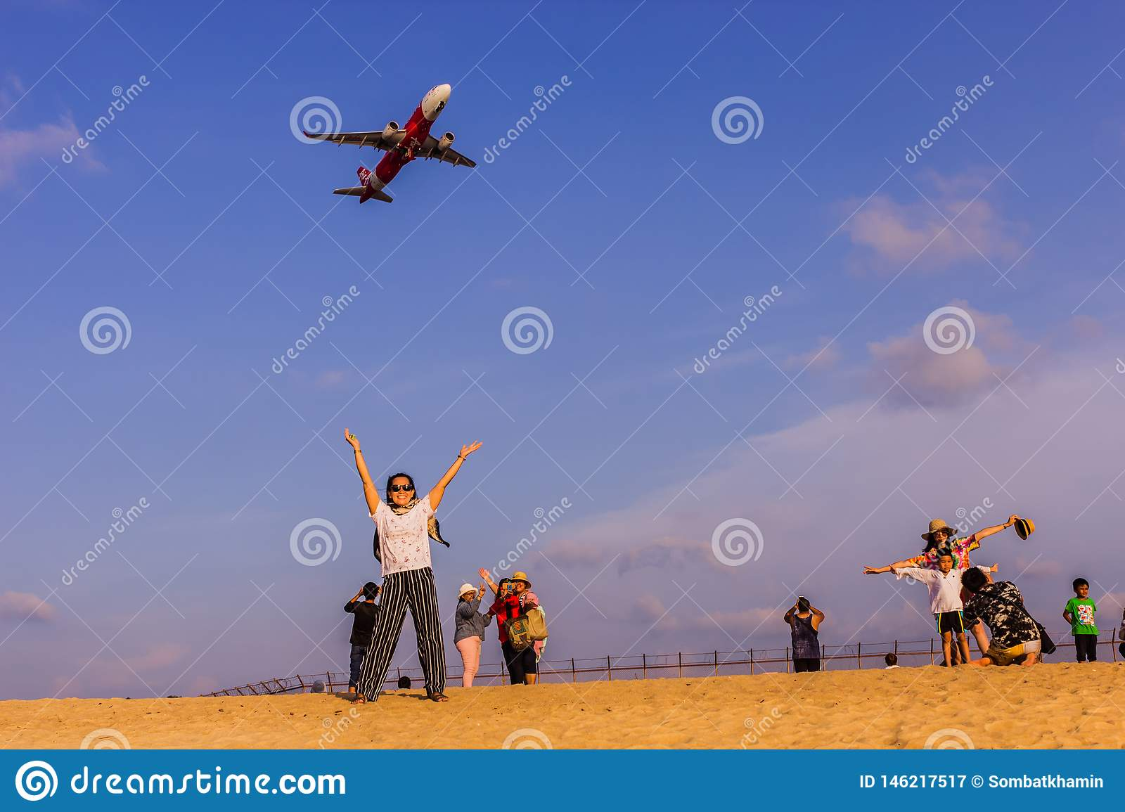 Phuket, Thailand - April 14, 2019: Tourists enjoy taking a picture with the airplane flying over them as the background, at the