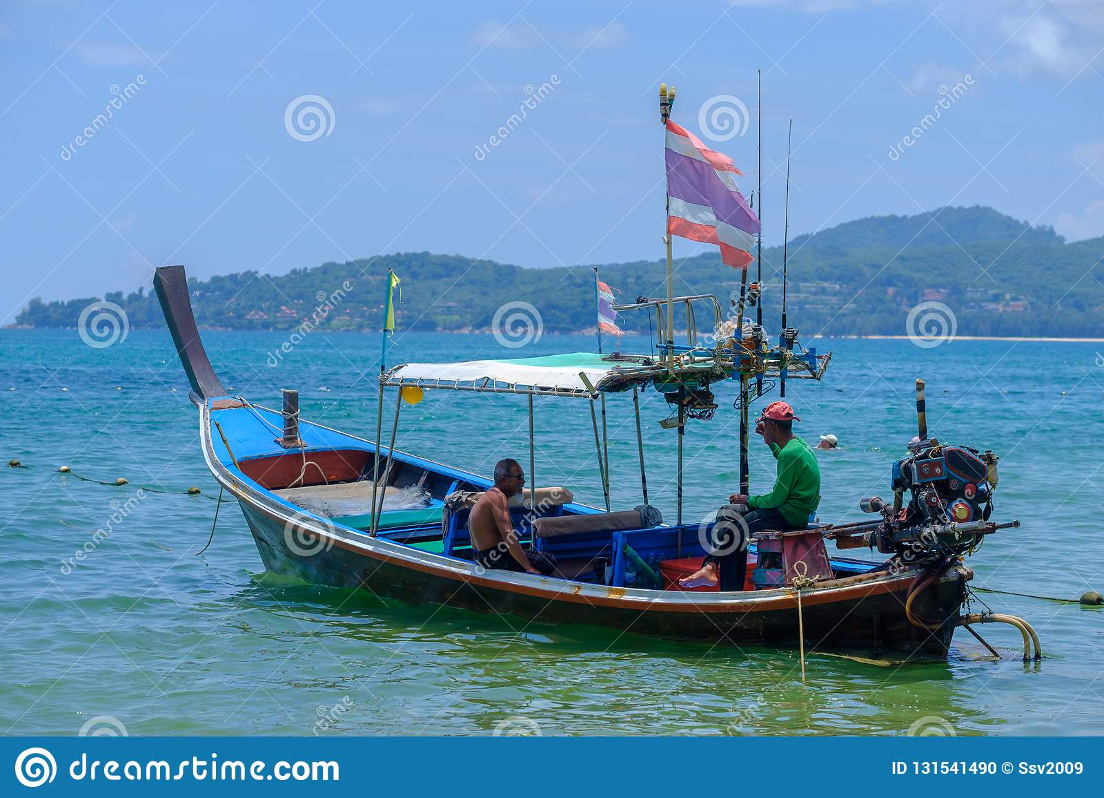Phuket thailand 08/05/2018 - Vissers die in zijn lange staartboot zitten