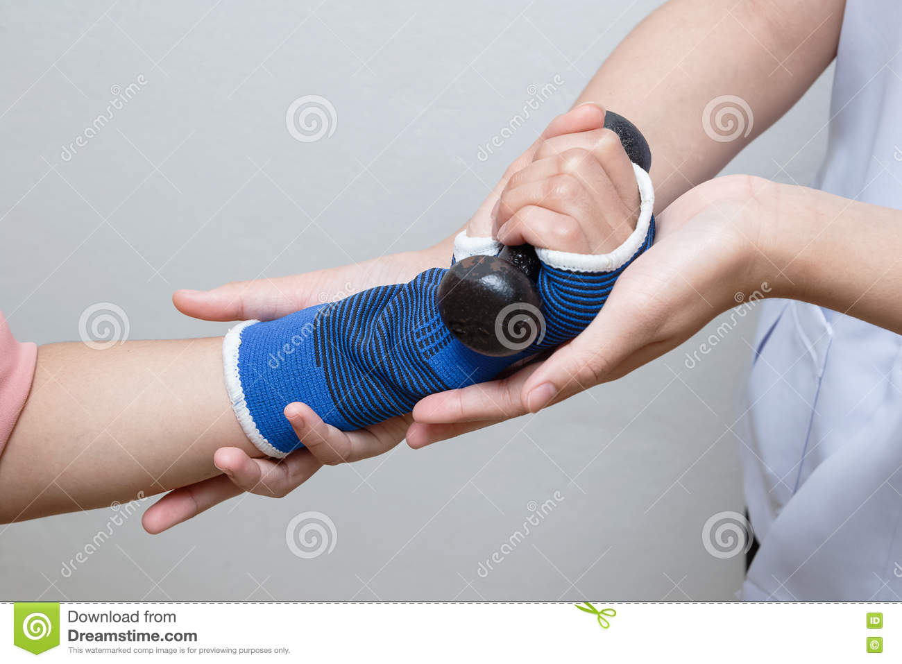Physical therapist assisting patient woman in lifting dumbbells