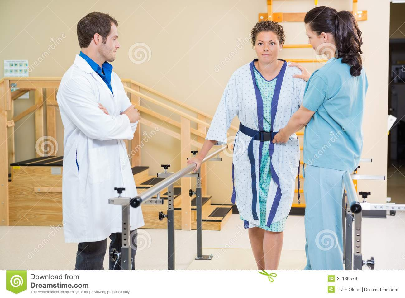 Physical Therapist With Doctor Assisting Female
