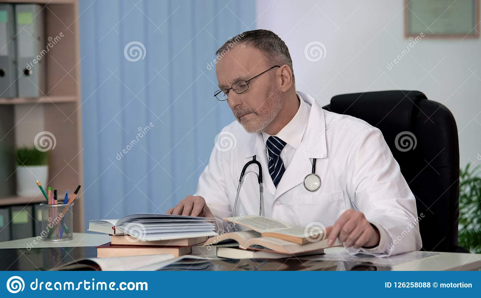 Physician reading medical books searching information about rare disease science